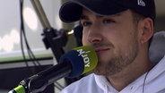 Das Bild zeigt den Sänger Eli beim Auftritt am Reeperbus. © N-JOY / NDR Foto: N-JOY / NDR