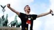 Per Mertesacker feiert seinen Sieg bei der WM 2014 in Berlin. © dpa-Bildfunk Fotograf: Daniel Naupold/dpa