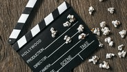 Das Bild zeigt eine Filmklappe, die auf einem Holztisch mit Popcorn liegt. © imago / westend61 Foto: westend61