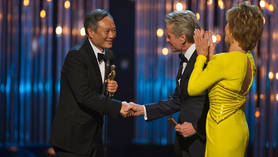 Gerührt nimmt der Regisseur Ang Lee seinen Oscar von Jane Fonda und Michael Douglas bei den 85. Oscars entgegen. © A.M.P.A.S./Michael Yada