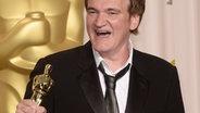 """Regisseur Quentin Tarantino mit seinem Oscar fürs beste Drehbuch für """"Django Unchained"""" bei den Motion Academy Picture Awards 2013 in die Luft © dpa bildfunk/ Paul Buck"""