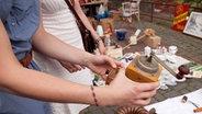 Eine Frau hält auf einem Flohmarkt eine kleine Kaffeemühle in der Hand. © dpa Picture Alliance