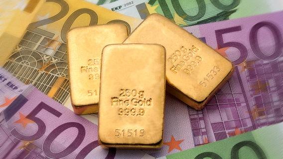 Goldstücke vor Geld. © fotolia Foto: Gina Sanders