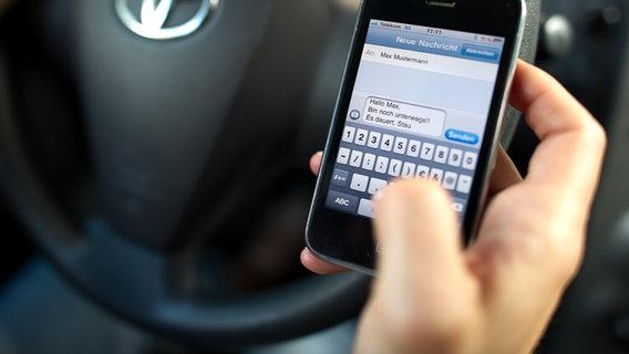 Mann schreibt SMS am Steuer.