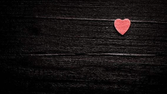 Ein kleines rotes Herz auf Holz. © Photocase / Maspi Foto: Maspi