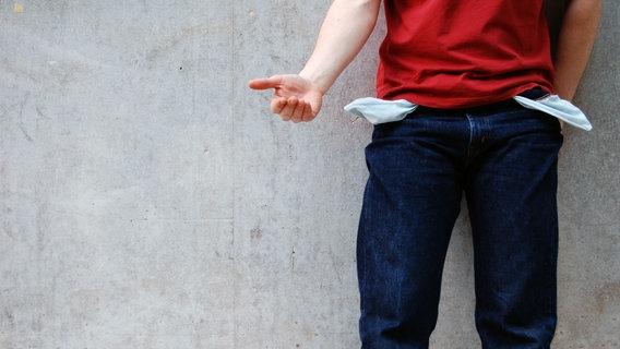 Ein Mann trägt eine Hose mit umgekehrten Taschen und hält die Hand auf. © photocase / AllzweckJack Foto: AllzweckJack