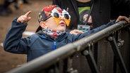 Ein Kind mit Ohrstöpseln und Eiscreme-Sonnenbrille feiert  dem Hurricane-Gelände 2018 in Scheeßel. © NDR Foto: Julian Rausche