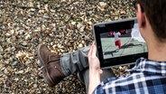 Junge guckt sich ein Musikvideo auf dem iPad an. © NDR / Friederike Göckeler Foto:  Friederike Göckeler
