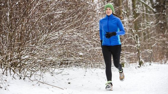 Junge Frau, Joggerin, bei einem winterlichen Lauf in einem verschneiten Wald. © imago Foto: Jochen Tack