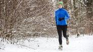 Junge Frau, Joggerin, bei einem winterlichen Lauf in einem verschneiten Wald. © imago Fotograf: Jochen Tack