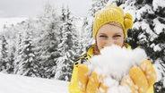 Junge Frau mit Pudelmütze spielt mit Schnee © imago/Westend61