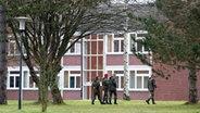 Soldaten laufen an einem Kasernengebäude vorbei. © dpa Foto: Tobias Kleinschmidt