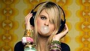 junge Frau mit Kaugummi und Kopfhörern © fotolia Fotograf: Alex Hagmann