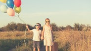 Zwei junge Kinder halten einige Luftballons. © photocase Foto: altanaka