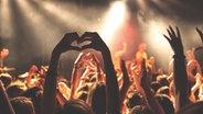 Eine Konzertbesucherin formt mit ihren Händen ein Herz. © http://creativecommons.org/publicdomain/zero/1.0/ Fotograf: Anthony DELANOIX