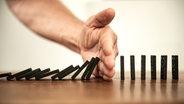 Eine Hand hält eine Kettenreaktion von Dominosteinen auf. © complize / photocase.de Foto: complize / photocase.de