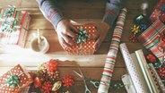 Das Foto zeigt die Hände einer Person, die ein Geschenk einpackt. © imago/Westend61 Fotograf: imago/Westend61
