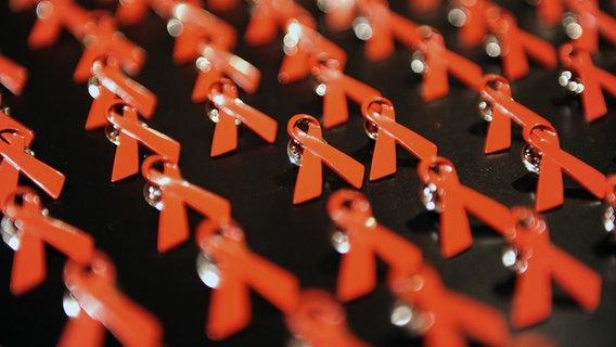 Rote AIDS-Schleifen © dpa - Bildfunk Foto: Jens Kalaene