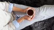 Eine Frau sitzt mit einem Kaffee auf dem Sofa. © s_karau / photocase.de Foto: s_karau / photocase.de