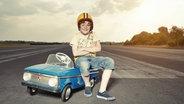 Ein kleiner Junge sitzt stolz auf seinem Spielzeugauto. © imago/Westend61 Fotograf: Westend61