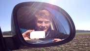 Ein junger Mann schaut in den Außenspiegel eines Autos und macht ein Selfie. © fotolia Foto: grafikplusfoto