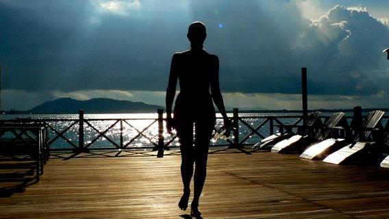 Die Silhouette einer Frau vor einem See im Sonnenuntergang. © Gurkentanz / photocase.de Foto: Gurkentanz / photocase.de