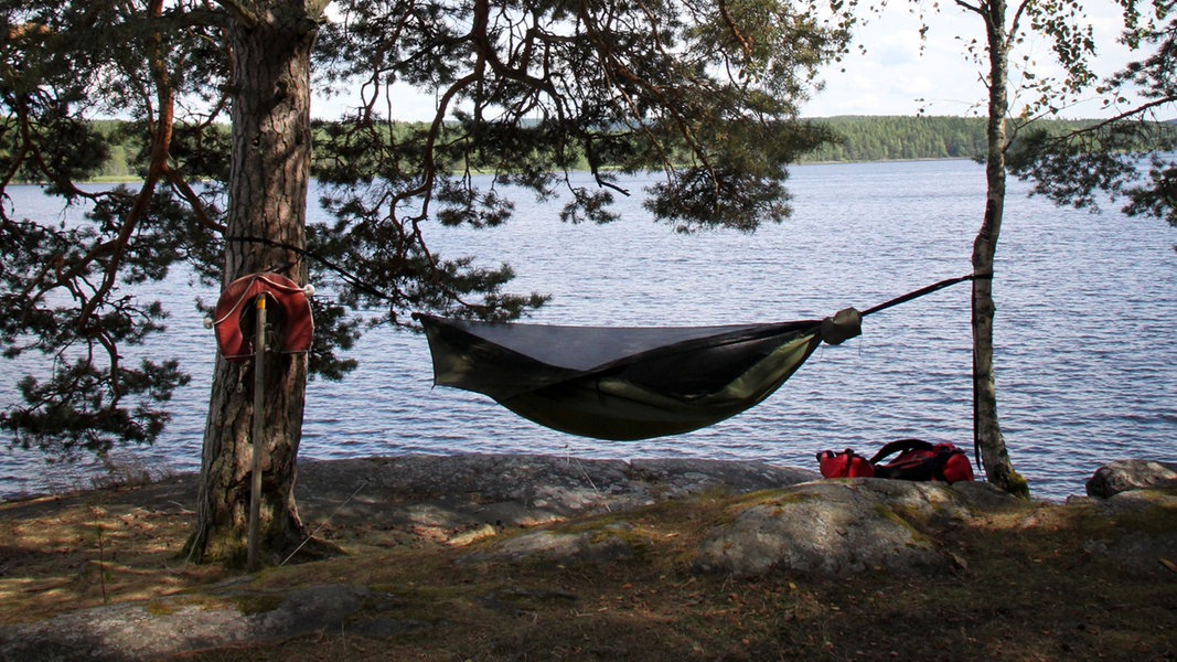 Ein Baumzelt ist an einem See zwischen zwei Bäumen aufgespannt. © ryu-tako / photocase.de Foto: ryu-tako / photocase.de