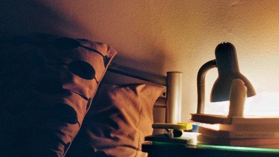 Neben einem Bett leuchtet eine Lampe auf dem Nachttisch. © photocase.de / John Dow Foto: photocase.de / John Dow