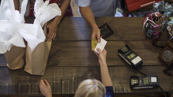 Jemand bezahlt an einer Kasse. © imago/Westend61 Foto: Westend61