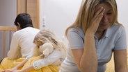 Ein Kind sitzt zwischen den streitenden Eltern. © picture alliance / dpa