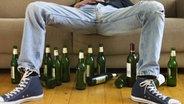 Zu sehen sind die Beine eines Mannes und viele Bierflaschen, die auf dem Boden stehen. © imago/Westend61 Fotograf: Westend61