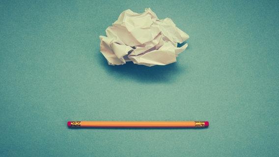 Ein zerknüllter Zettel und ein Bleistift mit Radiergummis auf beiden Seiten. © suze / photocase.de Foto: suze / photocase.de
