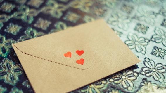 Ein Brief mit drei kleinen Herzchen liegt auf einem Tisch. © Eliza / photocase.de Foto: Eliza / photocase.de