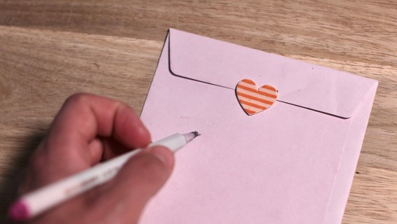 Ein Umschlag mit einem Herz, darunter eine Hand, die einen Stift hält. © pontchen / photocase.de Foto: pontchen / photocase.de