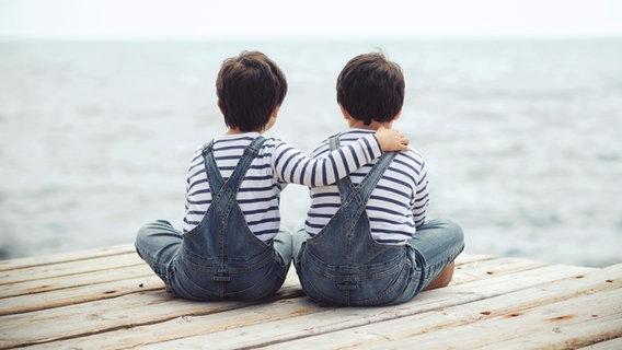 Zwei Jungs in gleichen Klamotten sitzen nebeneinander und sind von hinten zu sehen. © estherm / photocase.de Foto: estherm / photocase.de