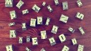 Auf einem Tisch liegen mehrere Stempel mit Buchstaben drauf. © misterQM / photocase.de