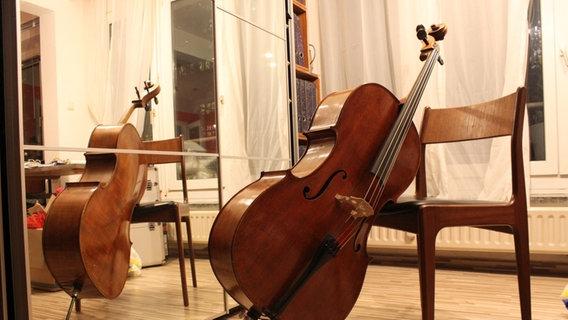 Ein Cello steht vor einem Stuhl
