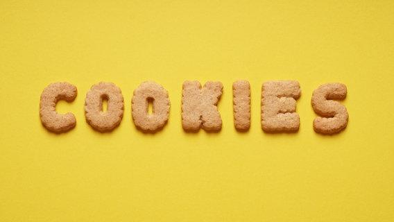 Auf gelbem Hintergrund ist aus Keksen das Wort Cookies gelegt. © axelbueckert / photocase.de Foto: axelbueckert / photocase.de