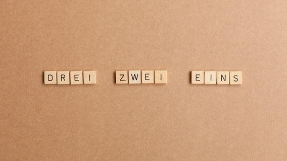 """Aus Würfeln mit Buchstaben stehen die Worte """"Drei, zwei, eins"""" geschrieben. © go2 / photocase.de"""