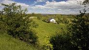 Einzelnes Haus in einer  Wald- und Wiesenlandschaft © picture alliance / blickwinkel