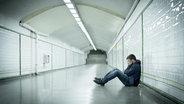 Ein junger Mann sitzt deprimiert auf dem Boden.  Fotograf: Focus Pocus LTD