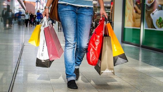 Eine Passantin trägt Einkaufstüten durch ein Einkaufszentrum © Fotolia Foto: jonasginter