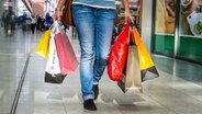Eine Passantin trägt Einkaufstüten durch ein Einkaufszentrum © Fotolia Fotograf: jonasginter