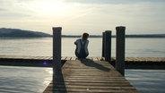 Eine Frau sitzt einsam auf einem Steg. © bunnyface / photocase.de Foto: bunnyface / photocase.de