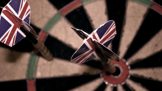 Zwei Dartpfeile mit der englischen Flagge als Flight stecken in einem Dartboard. © madochab / photocase.de Foto: madochab / photocase.de
