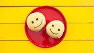 Auf einem Teller liegen zwei Berliner mit einem lächelnden Gesicht. © imago/CHROMORANGE Fotograf: CHROMORANGE