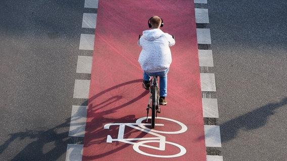 Ein Fahrradfahrer fährt mit Kopfhörern auf einem Radweg. © picture alliance / Wolfram Steinberg Foto: Wolfram Steinberg