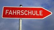 """Auf einem roten Wegweiser-Schild steht """"Fahrschule"""". © Imago/Steinach"""