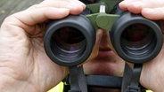 Mann schaut durch Fernglas ©  picture alliance/ dpa