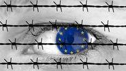 Zu sehen ist ein Auge hinter einem Stacheldrahtzaun. Im Innern des Auges sind Europasterne zu sehen. © picture alliance/chromorange Fotograf: CHROMORANGE / Ralph Peters